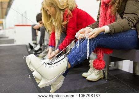 people, winter sport and leisure concept - close up of woman wearing and lacing skates on skating rink