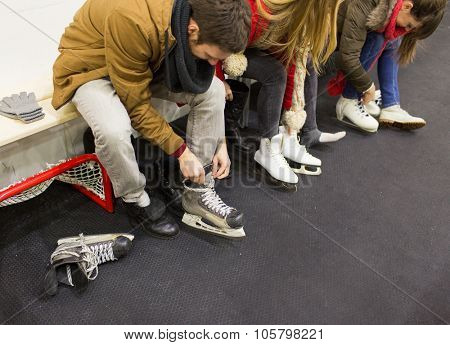 people, winter sport and leisure concept - close up of friends wearing and lacing skates on skating rink