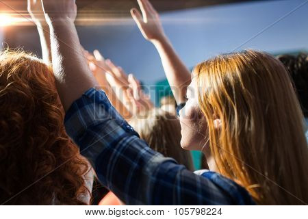 party, holidays, music, nightlife and people concept - close up of happy people at concert in night club waving hands