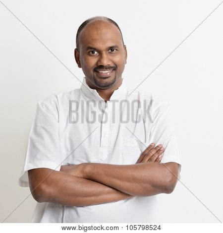 Portrait of mature casual business Indian man smiling, standing on plain background with shadow.