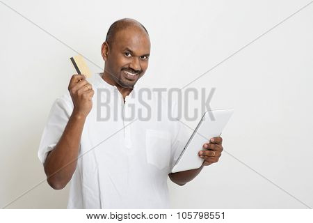 Portrait of mature Indian man shopping online using tablet pc, making payment by credit card. Asian man standing on plain background with shadow and copy space.