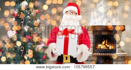 christmas, holidays and people concept - man in costume of santa claus with gift box and tree over home fireplace and lights background