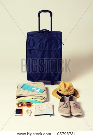 summer vacation, tourism and objects concept - travel bag, map, air ticket and clothes with personal stuff
