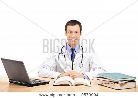 A Doctor Posing In His Office, With Laptop And Many Book