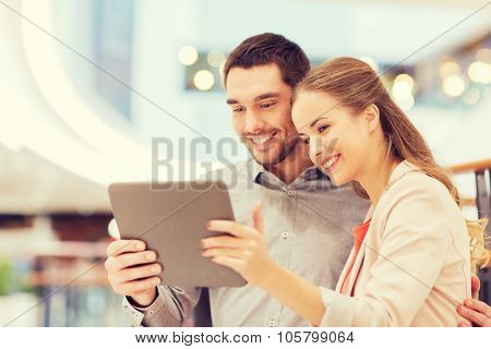 shopping, technology and people concept - happy couple with tablet pc taking selfie in mall or business center