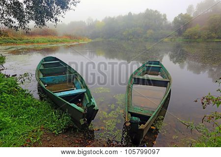 Two wooden boats on morning river