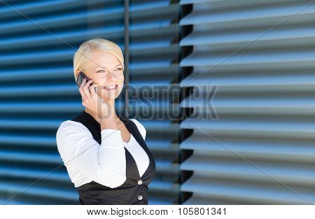 Beautiful businesswoman arranging a meeting by the phone being outdoor.