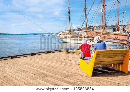 Elderly couple on bench of pier, Oslo, Norway