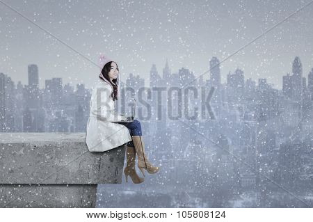Girl In Winter Coat Using Laptop On The Roof