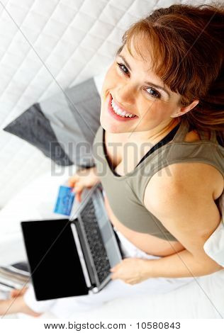 Smiling beautiful pregnant female on sofa with the laptop and credit card.