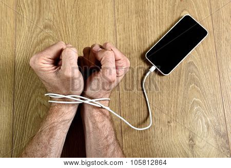 Man Hands Wrapped On Wrists With Mobile Phone Cable Handcuffed In Smart Phone Networking Addiction C