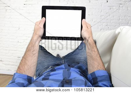 Man Lying On Home Couch Using Digital Tablet Pad In Portable Internet Technology