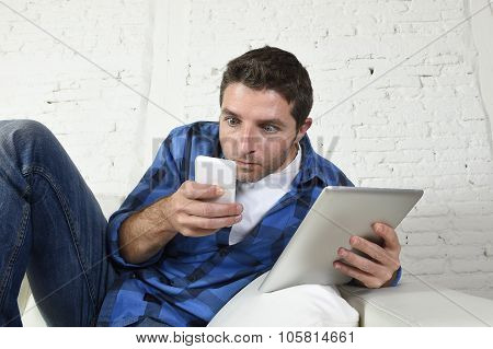 Young Internet And Technology Addict Man Networking With Mobile Phone And Digital Tablet