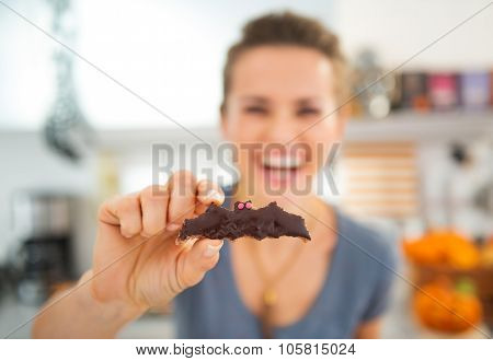 Closeup On Halloween Bat Biscuit In Hand Of Smiling Young Woman
