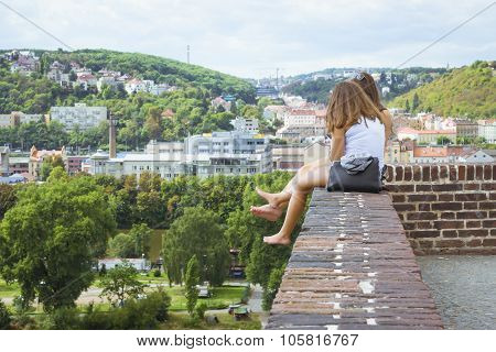 Two Girls Sitting On The Edge Of The Wall, His Feet Dangling