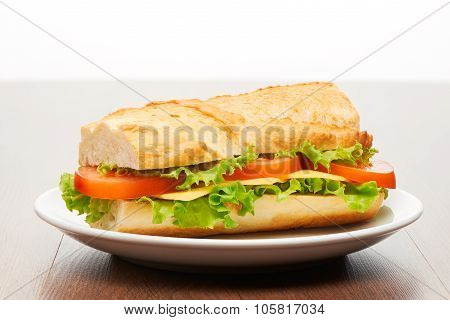 Tomato cheese and salad sandwich from fresh baguette on white ceramic plate on bright light brown wo