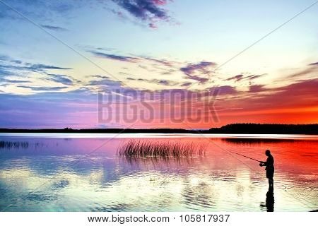A fisherman with rod on a lake at sunset