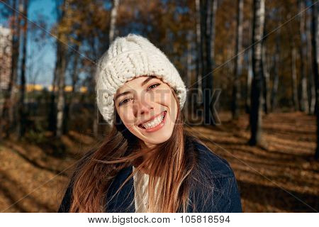 Portrait Of A Beautiful Very Cute Autumn Girl A Knitted Cap In City Park. Fall Woman Portrait Of Hap