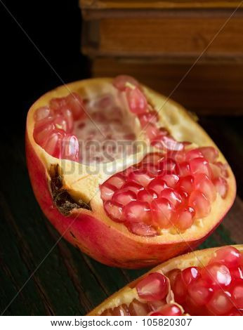 Half Of Pomegranate In Front Of Old Books