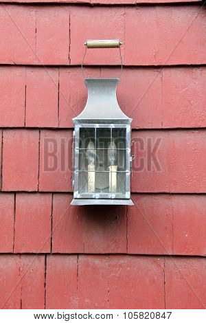 Old, rustic lantern hanging on red shingles