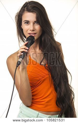 Beauteous woman in orange shirt with microphone.