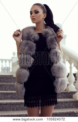 7d721aa1374 fashion outdoor photo of gorgeous woman with long dark hair wears luxurious  fur coat posing on stairs poster. ID  105824072