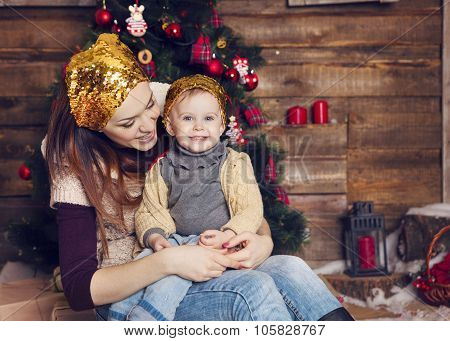 Stylish Mother And Her Child Celebrating Christmas In Room Over Christmas Tree