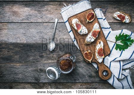 Tasty Snacks With Cheese Jam And Figs On Wood