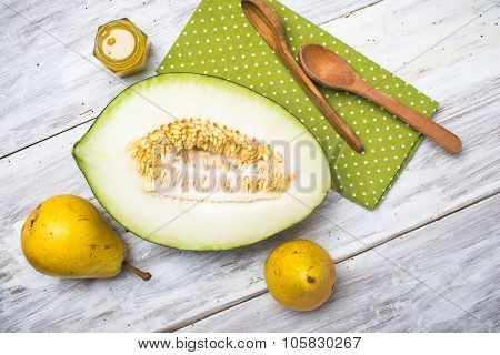 Cut Melon With Honey And Yellow Pears On Wood
