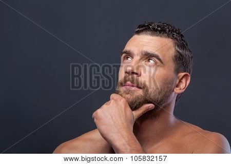 Attractive bare bearded guy is very pensive