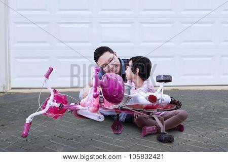 Man And His Daughter Repairing Bicycle