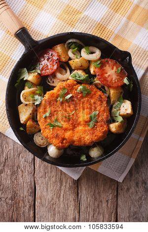 German Weiner Schnitzel With Vegetables In A Pan. Vertical Top View