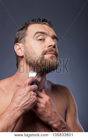 Cheerful bearded guy is caring of his appearance