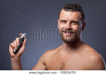 Cheerful young guy with beard and shaver