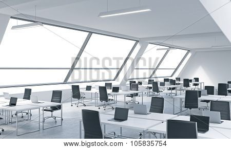 Workplaces In A Bright Modern Open Space Loft Office. White Tables Equipped By Modern Laptops And Bl