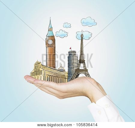 A Man's Hand Holds Sketches Of The Most Famous Places In Italy, Great Britain And France. The Concep