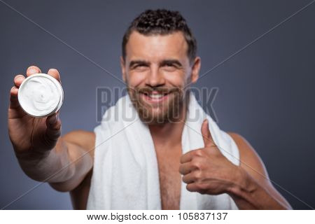 Cheerful bearded guy is caring of his skin