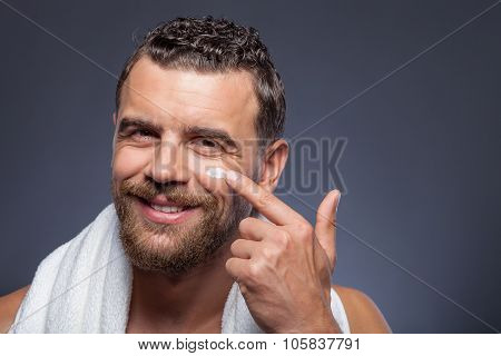 Handsome guy with beard is treating skin