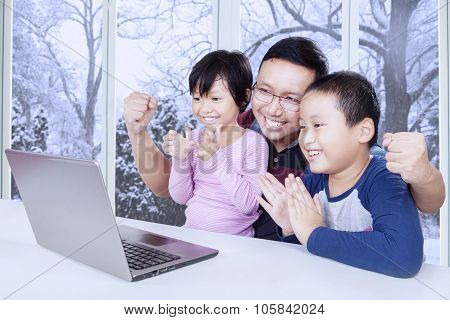 Two Cheerful Kids Clapping Hands With Their Dad
