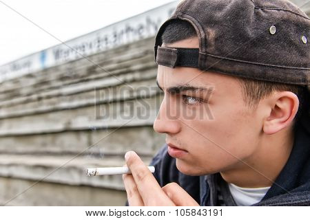 Teenage Boy Smoking Cigarette Outdoor. Concept Of Young People With Harmful Habits