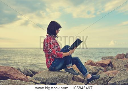 Young Hipster Girl Sitting On Rock With Book