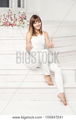 Portrait of happy smiling young beautiful woman in white casual clothing, showing thumbs up gesture,