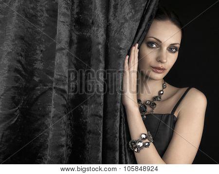 Beautiful woman behind the velvet curtain on dark background