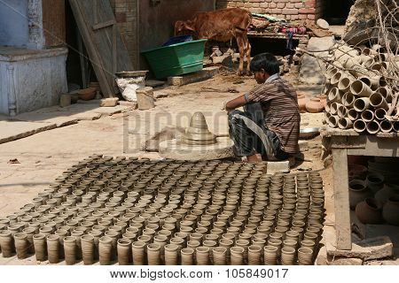 Indian boy making disposable cups from clay. Vrindavan, India.