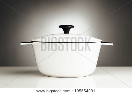white saucepan, kitchen pot on grey background