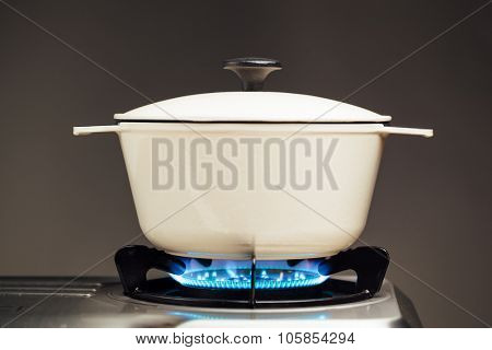 white cast iron saucepan on the gas stove