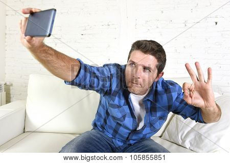Young Attractive 30S Man Taking Selfie Picture Or Self Video With Mobile Phone At Home Sitting On Co