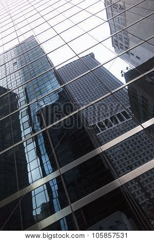 Glass Facade Of Skyscraper In New York Downtown Manhattan With Reflections Of Other Skyscrapers