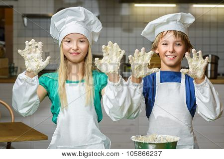 Funny happy chef boy width girl cooking at restaurant kitchen and knead the dough in a bowl