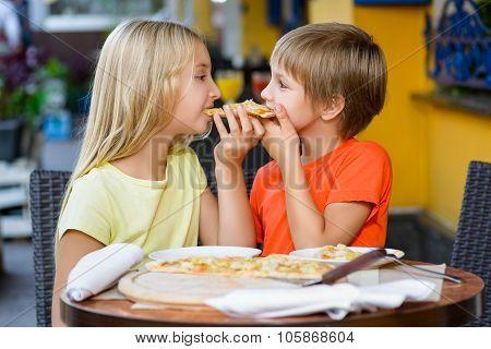 Happy children indoors eating pizza smiling